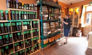 The shop assistant fills a bottle with whisky at the shop at the Springbank Distillery, Campbeltown, Kintyre, Argyll, Scotland.