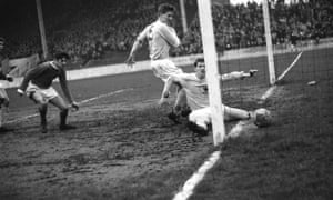 Mike Doyle, on the floor, fails to clear a George Best goal in a youth match against Manchester United.