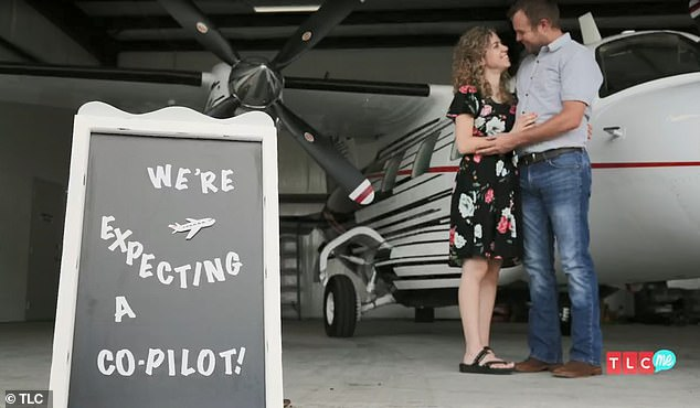 Flying together: Their 'We're expecting a co-pilot' sign comes after John David's flying-themed proposal