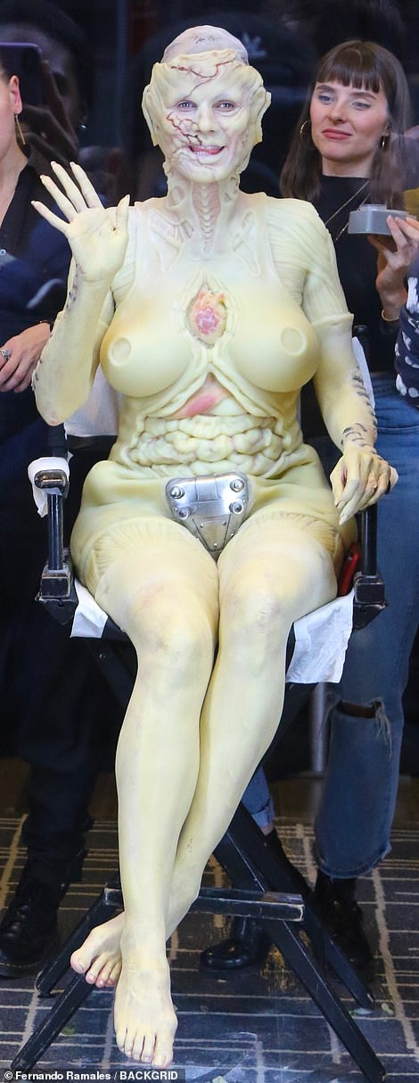 Spirit of the season: Heidi smiled and waved at fans as she sat in the shop window having her prosthetics applied