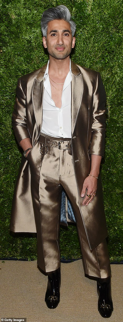 Shining: Queer Eye star Tan France looked stylish in a silky brown suit with a long evening coat and a partially unbuttoned white shirt