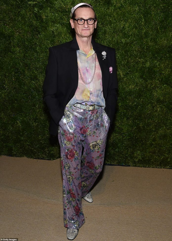 Fashion journalist Hamish Bowles paired a black jacket with a sheer pink and blue shirt and lavender trousers decorated with flowers