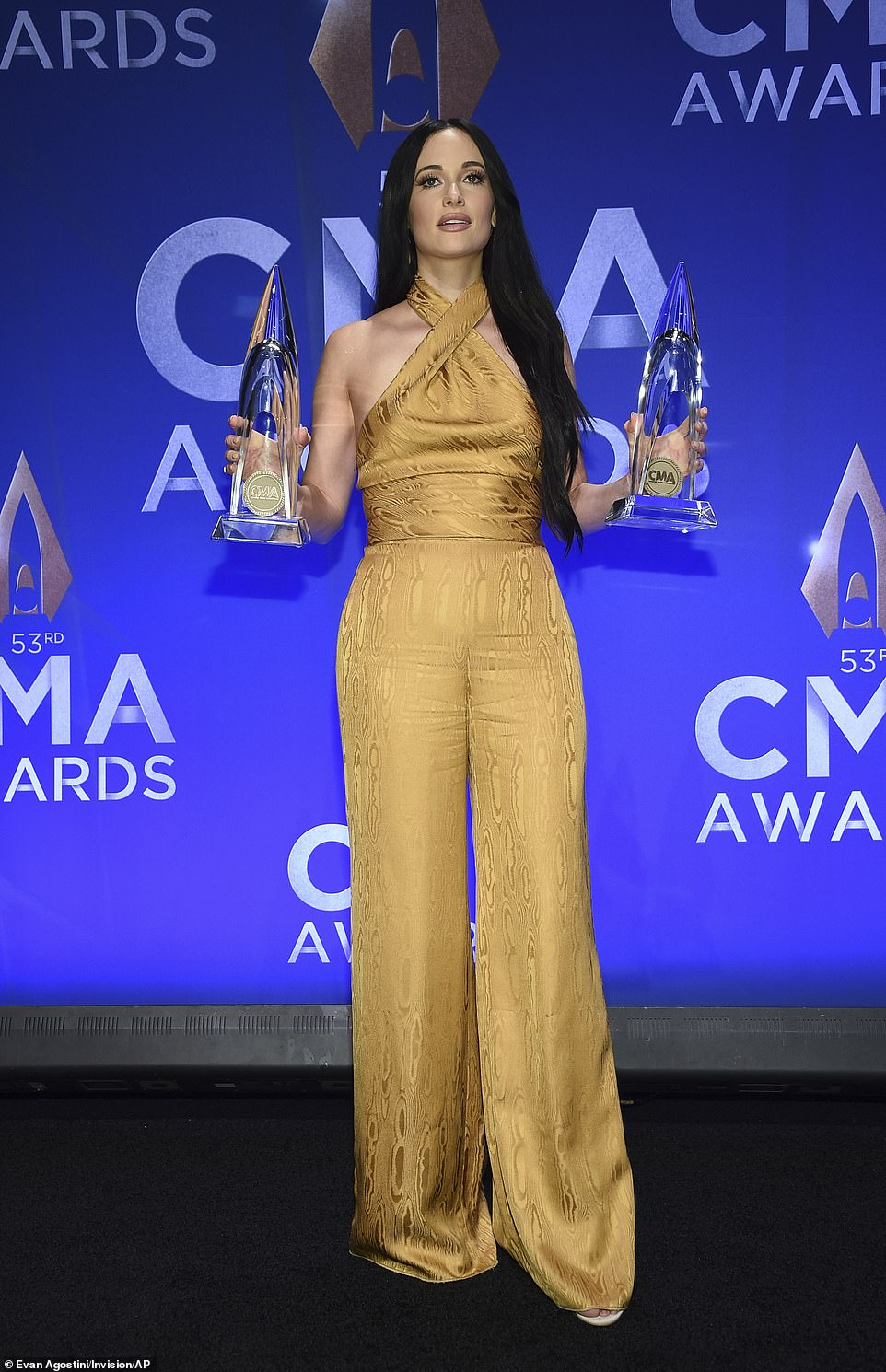 Dual winner: Kacey Musgraves holds up her two CMAs in the press room, one for Female Artist of the Year and one for Music Video of the Year for Rainbow