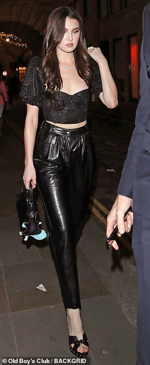 A vision in black: The 19-year old caught the eye in a cropped black top and matching high-slung leather trousers