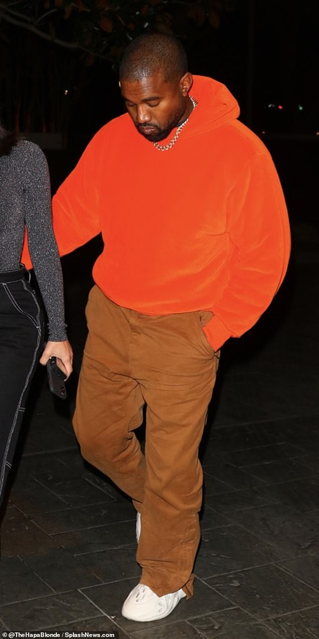 Keeping warm and comfortable:Kanye kept things casual in a bright red hoodie and ran colored trousers