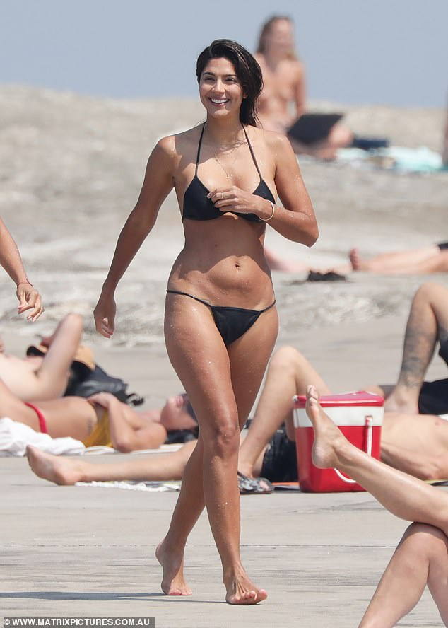 Beaming: Walking back, the stunner wowed beach-goers showing off her fabulous figure