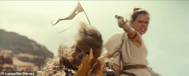 Blast them away: Rey uses a blaster with Chewbacca behind her