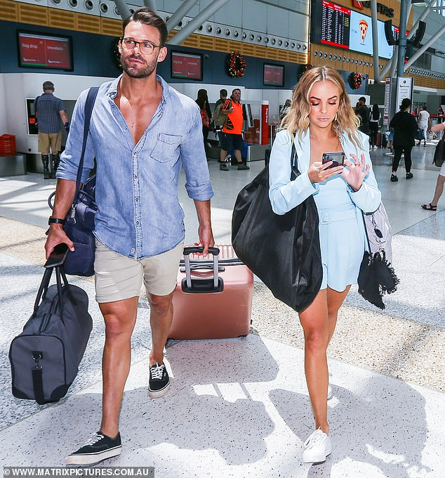 A match made in heaven? Angie Kent, 29, and Carlin Sterritt, 30, were glued to their phones at Sydney Airport on Friday following The Bachelorette finale