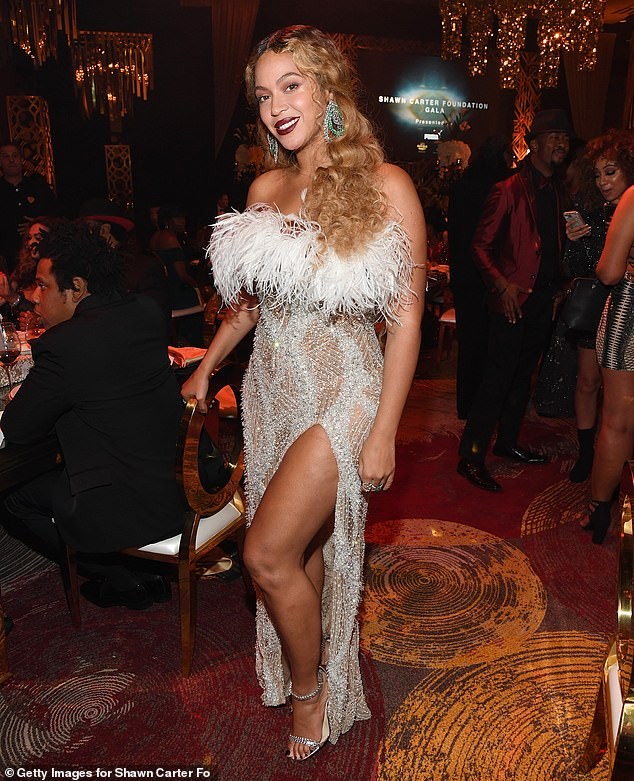 All eyes on her: Beyoncé, 38, lit up night two of her husband Jay-Z's Shawn Carter Foundation gala in a sparkling silver gown adorned with rhinestones at feathered; pictured with Jay-Z (L)