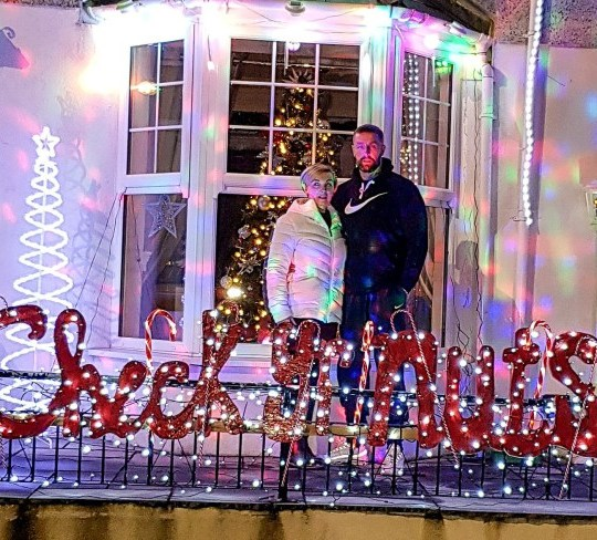 Christian Roach and his partner Nicola Richardson, 39, in front of the 'Check Yr Nuts' sign lights. Christian Roach, 41, has decorated his home in Rhondda, Wales, with Christmas lights that spell out ??????check your nuts??? after successfully beating testicular cancer. See SWNS story SWOCnuts. A man has decorated his house with Christmas lights that spell ???check your nuts??? after beating testicular cancer. Cancer survivor Christian Roach was suffering with testicular cancer in December last year and was unable to enjoy Christmas over fears for his health. Christian, from, needed life-saving surgery to remove one of his testicles after he went to the doctors worried about a lump on his private parts shortly after Christmas. Now aged 41, Christian is cancer free and to celebrate Christmas this year, has installed a set of fairy lights on the front of his house to deliver an important message.