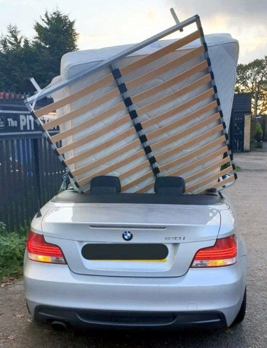 "A BMW with a mattress and bed frame upright on the back seat, which was stopped by police in Colchester, Essex. See SWNS copy SWCAbed: A BMW convertible was stopped by police after it was spotted being used to transport a double bed. A picture posted online by Essex Police shows the roof down and a mattress and bed frame upright on the back seat. Officers had been on patrol in Colchester Road between Colchester and Basildon and wrote about the ""insecure load"" on Twitter."