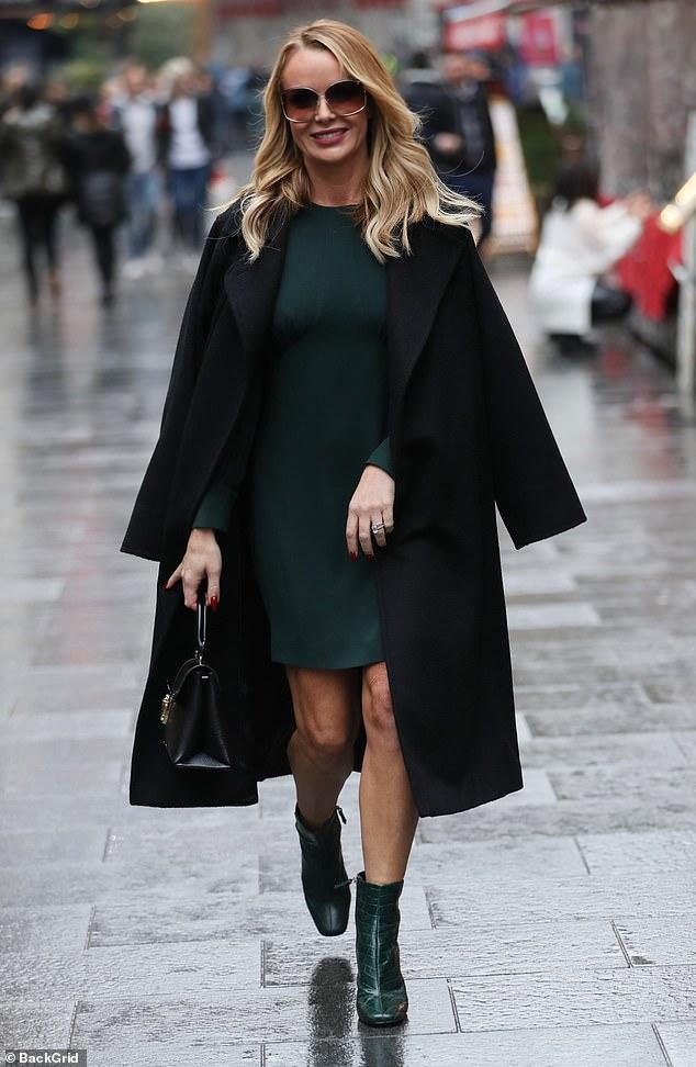 Glamorous:Amanda Holden oozed sophistication in a festive forest green ensemble and oversized brown sunglasses as she left the Heart Radio Studios on Thursday