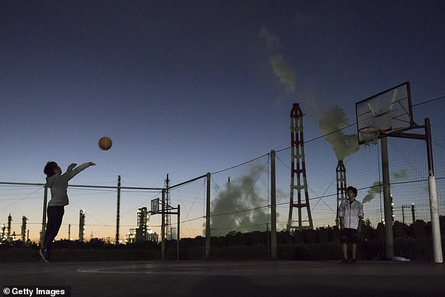 Research found that when countries around the world have closed factories or roads, pollution has dropped and hospitalisations for lung and heart conditions went down (Pictured: People play basketball near polluting factories in Kamisu, Japan)