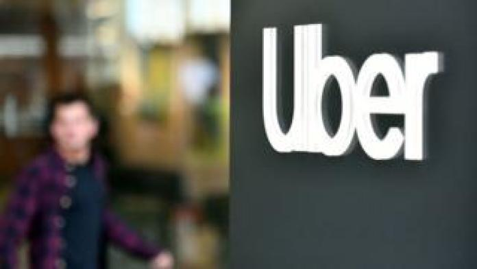 An Uber logo is seen on a sign outside the company's headquarters location as people protest nearby in San Francisco