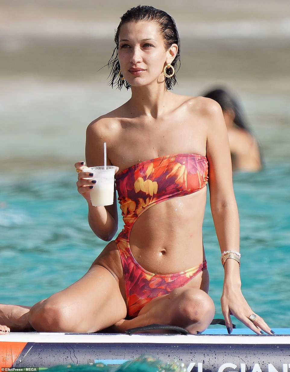 Glistening: Bella looked refreshed as she enjoyed her drink in the water