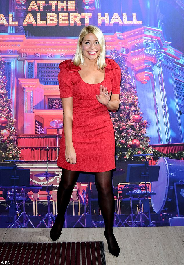 Getting into the spirit of things: The TV presenter, 38, dressed for the occasion, wearing a bright red dress with bow detailing on the shoulders