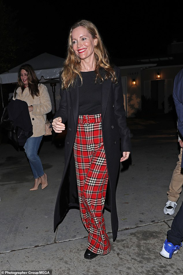 Beauty: The actress, 47, exuded style as she left the bash in a black tailored coat and red plaid high-waisted trousers