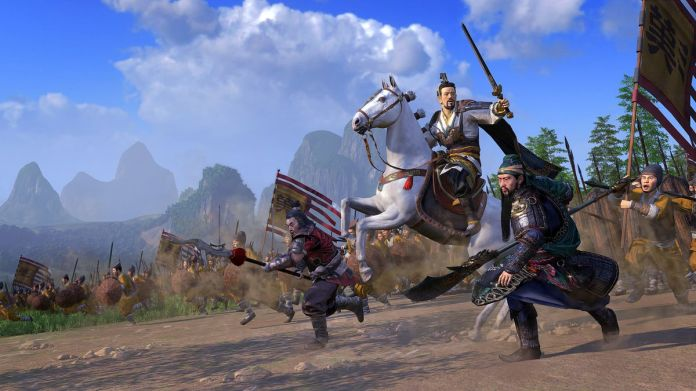 a Chinese military officer on a white horse brandishing a sword leads his forces into battle in Total War: Three Kingdoms
