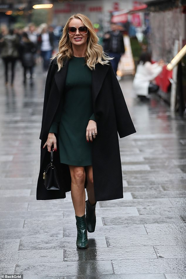 Style:She carried a shiny leather bag by her side and displayed her svelte pins in the knee-length green dress
