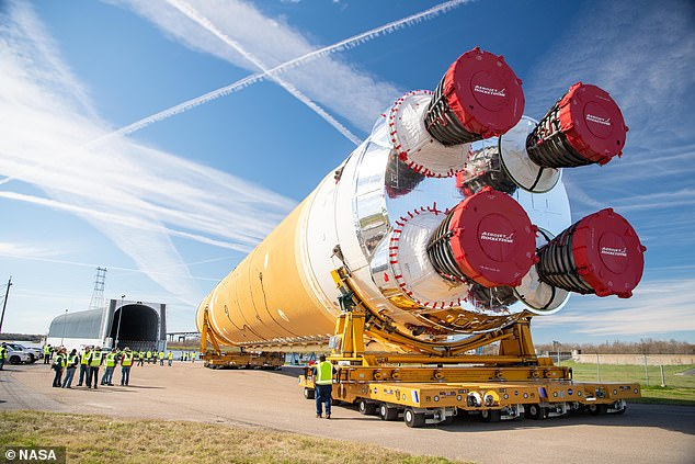 The most powerful rocket ever built has emerged from its hanger and has been loaded onto a barge (left) for transport from Louisiana to Mississippi for testing
