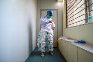 A doctor puts on a protective suit before starting work in the isolation ward of a hospital in Wuhan on 30 January.