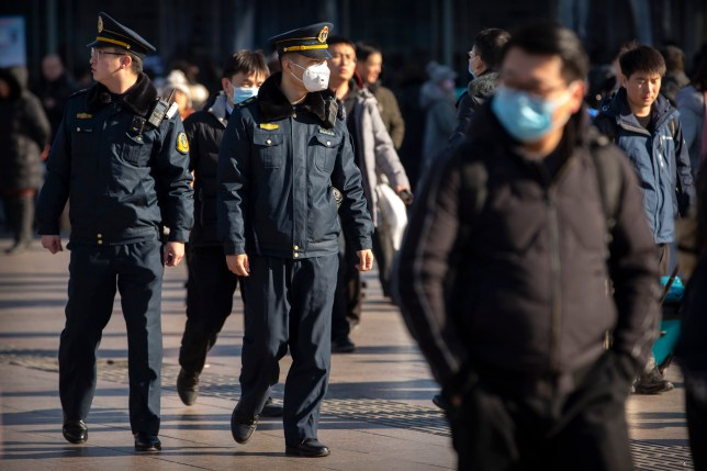 A security officer wears a face mask as he patrols outside of the Beijing Railway Station in Beijing, Monday, Jan. 20, 2020. China reported Monday a sharp rise in the number of people infected with a new coronavirus, including the first cases in the capital. The outbreak coincides with the country's busiest travel period, as millions board trains and planes for the Lunar New Year holidays. (AP Photo/Mark Schiefelbein)