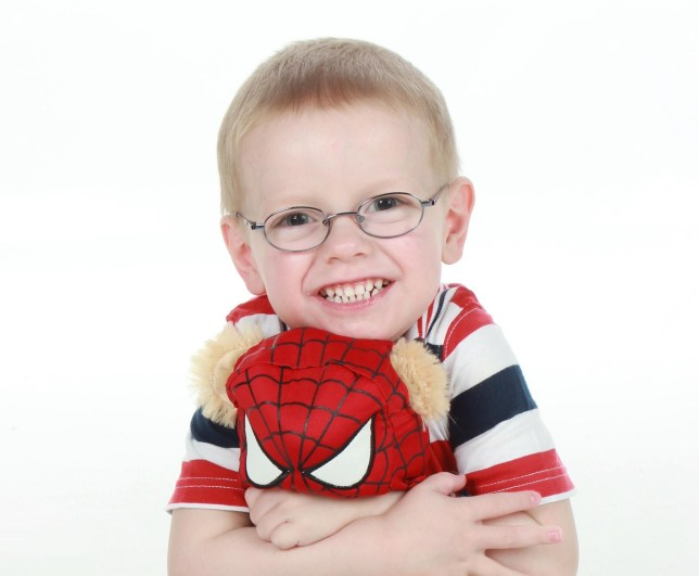 Four-year-old Henry cuddling a Spiderman teddy