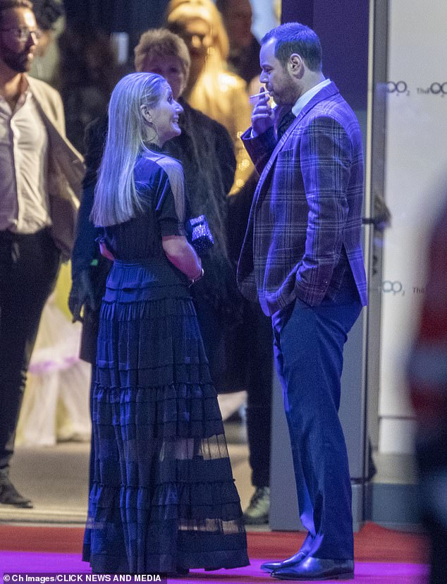 Puffing away:Danny Dyer was chatting away to his wife Joanne Mas as he smoked a cigarette and looked sharp in a checked grey suit