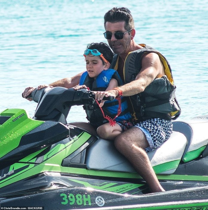 Father and son:The X Factor supremo, 60, looked chilled and content as he displayed his toned torso in a pair of monochrome shorts, before hitting the jet-skis with five-year-old Eric
