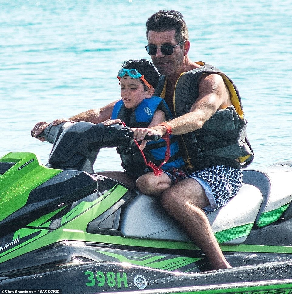 Father and son: The X Factor supremo, 60, looked chilled and content as he displayed his toned torso in a pair of monochrome shorts, before hitting the jet-skis with five-year-old Eric