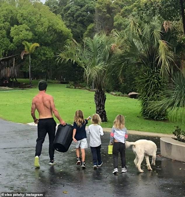 Putting it back: Elsa shared a snap of Chris, their children and pet dog Sunny walking towards a garden, with Thor star Chris holding the bin