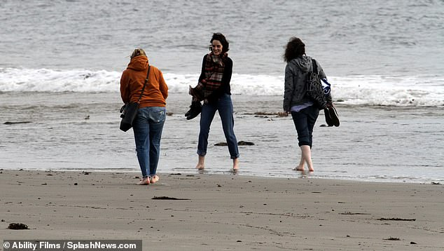 Banter: Michelle laughed as she took her shoes off for the quick paddle in the ocean