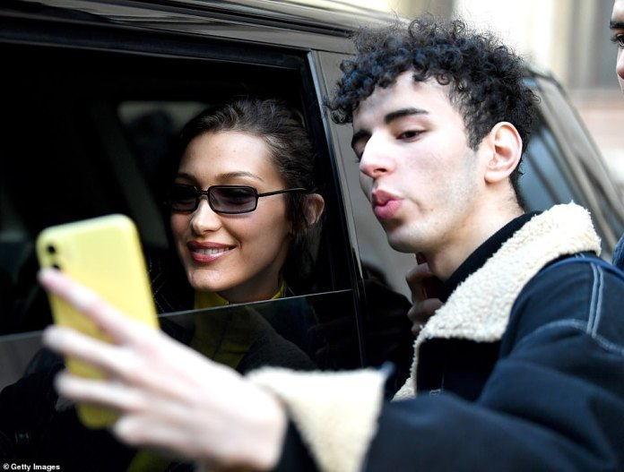 Thrilled: As she exited her hotel Bella also posed for a selfie with a delighted fan as she climbed into her car