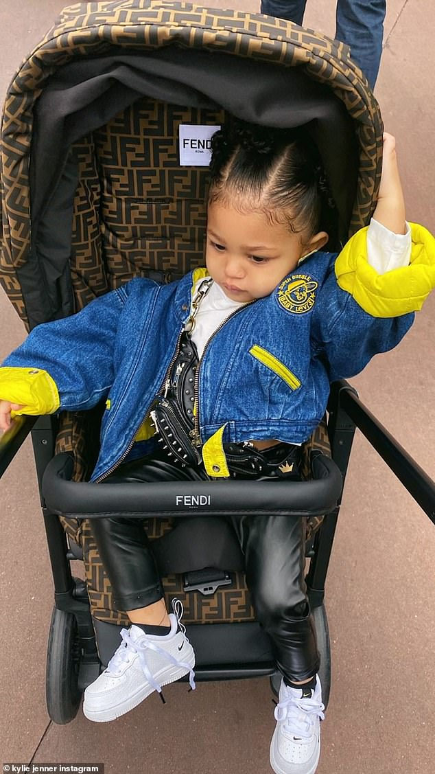 So stylish: Her child had on a Levi's jacket with PVC leggings and Bike sneakers; there also seemed to be a fanny pack around her chest