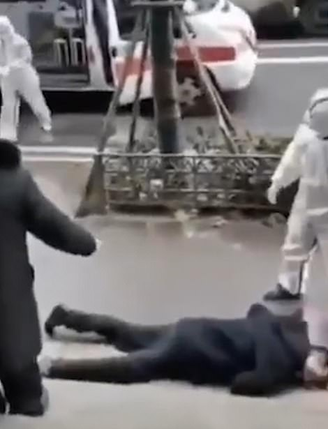 Medics attend to a collapsed person on a Wuhan sidewalk