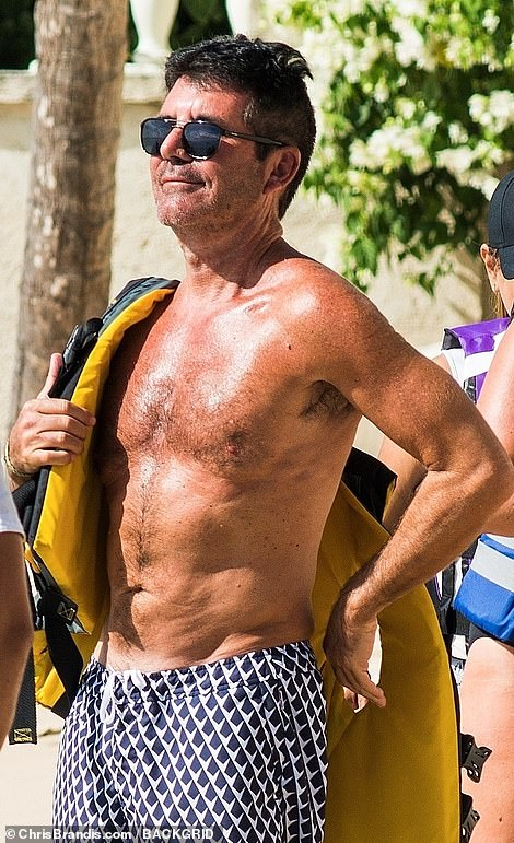 Safety first: Simon strapped himself into a yellow life jacket as he prepared for another jet ski ride during his annual jaunt to Barbados
