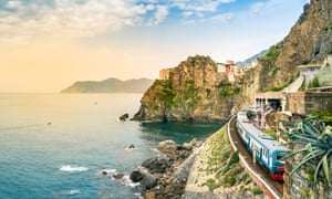 Manarola, Cinque Terre - train station in small village with colourful houses on cliff overlooking sea. Cinque Terre National Park with rugged coastline, Italy.