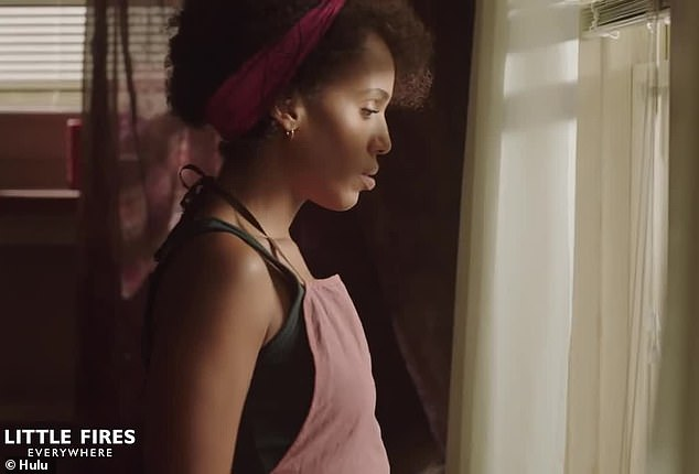 Another woman is seen at a window: Mia, played by Washington, stands in drabber surroundings