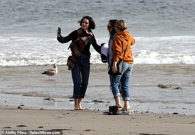 Relaxed:The Lady Mary Crawley star, 38, cut a casual figure in a black sweater and boyfriend jeans as she chatted with her pals, snapped some selfies and took a paddle in the sea