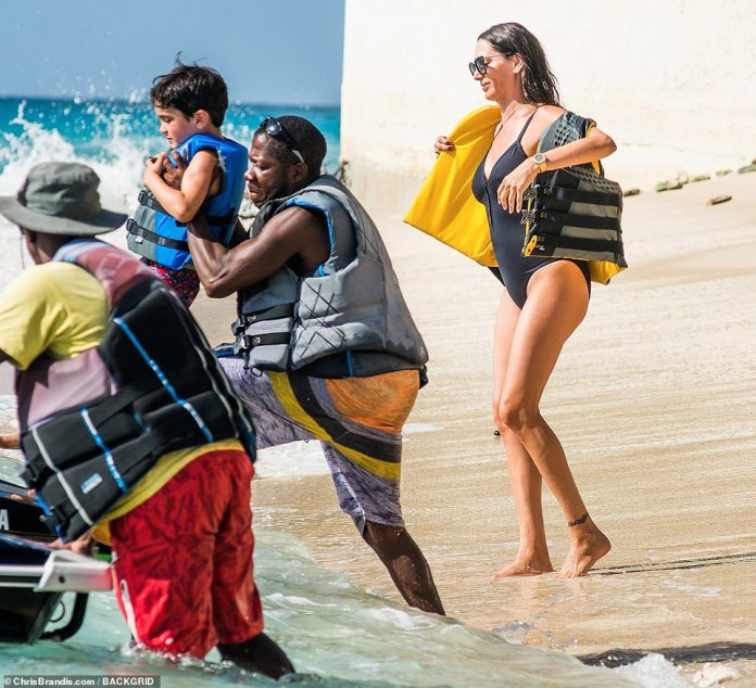 Helping hand: Little Eric was helped onto the jet ski as Lauren watched on from behind