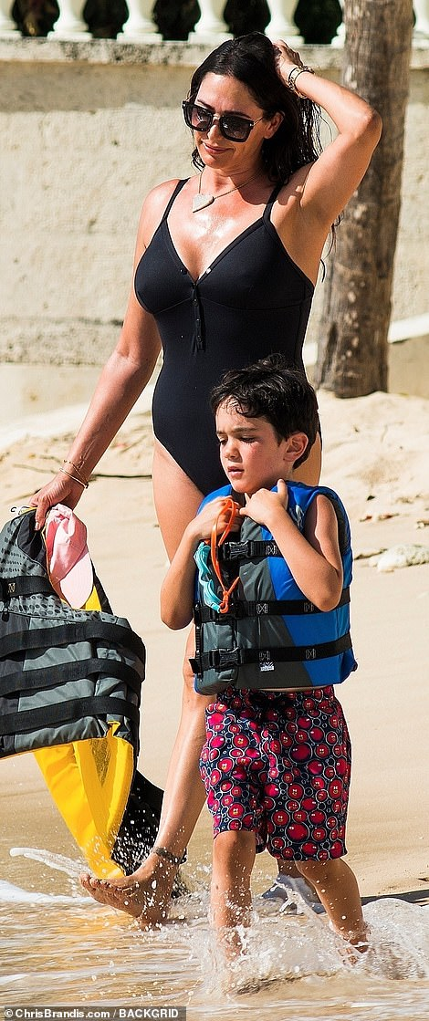 Tottering along: Eric walked alongside his mother as they headed for a spot of water sports