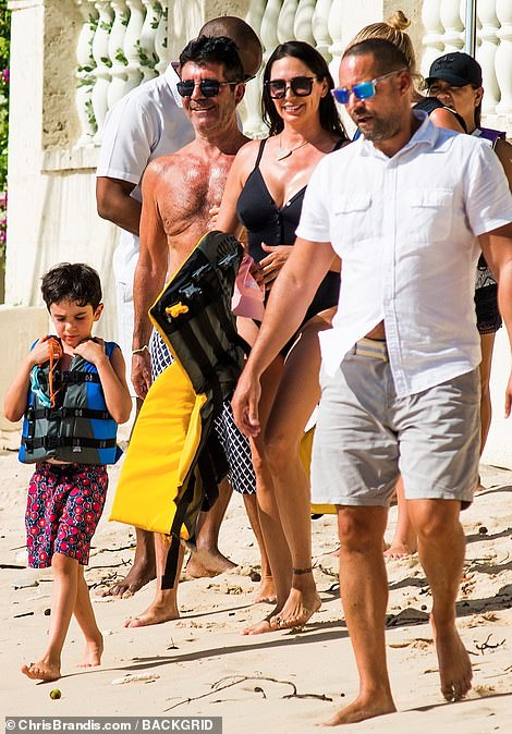 Full of joy: Simon and Lauren were full of smiles as they took their five-year-old son jet skiing in Barbados