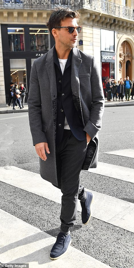 Relaxed: He donned agrey trench coat and tailored trousers as he headed into the fashion show