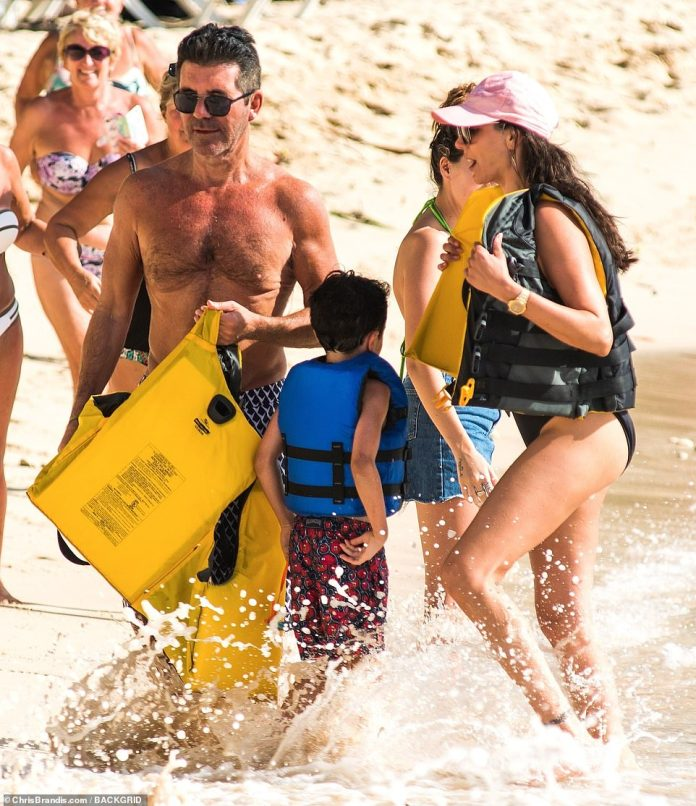 Popular: The family were surrounded by a group of excited tourists as they walked along the beach
