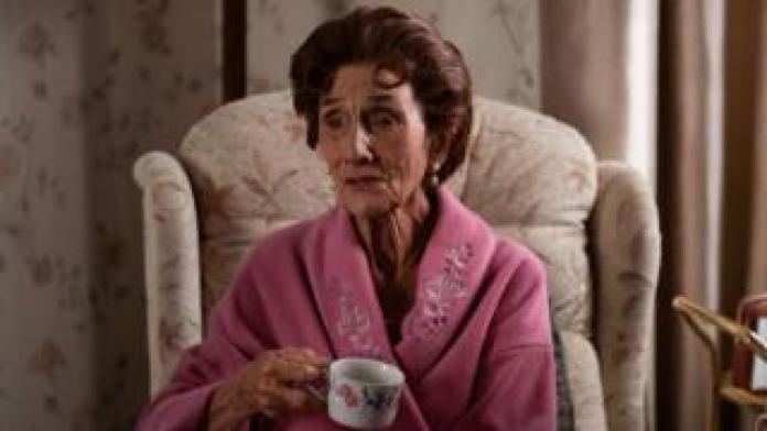 June Brown as Dot Branning in EastEnders, sitting in an armchair drinking a cup of tea