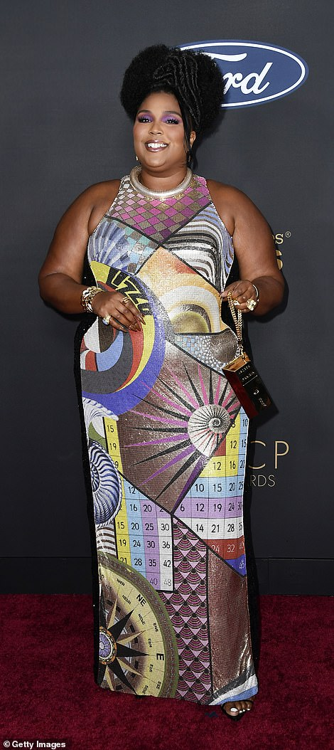 The Truth Hurts hitmaker accessorized with a gold clutch and an abundance of gold jewelry