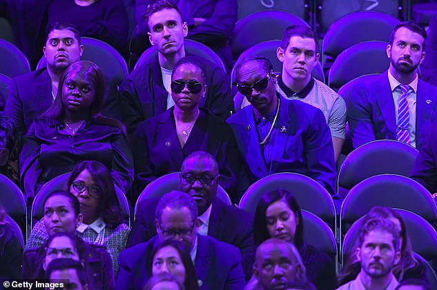 Snoop Dogg sits in the crowd, lit by purple light in honor of Kobe