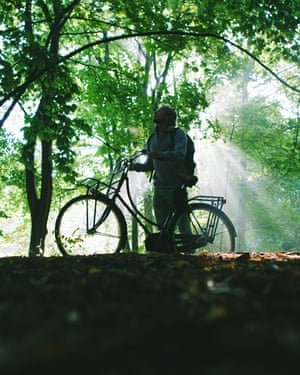 Person Standing Next To His Bicycle In The Forest And Looks Up.Light by autumns morning light shining through the leaves