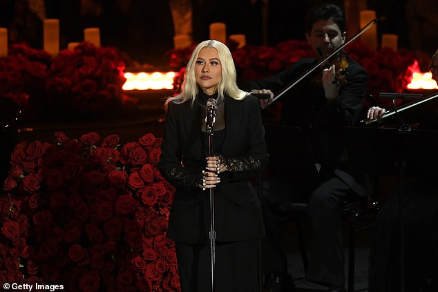 Somber look:The 39-year-old Genie In A Bottle singer had her long blonde hair worn down and parted in the middle. And the star added deep red lipstick as she sang Ave Maria