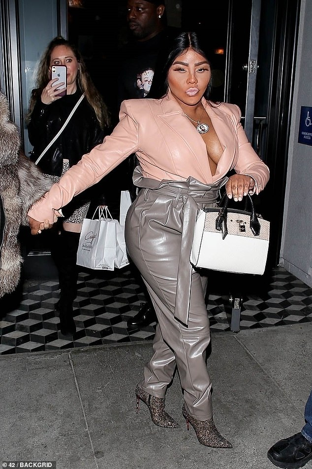 Flaunt it:The Crush On You rapper put on a busty display in a low-cut blazer and showcased her curvy assets in a pair of high-waisted leather pants